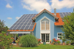 modern new built house and garden, rooftop with solar cells, blu
